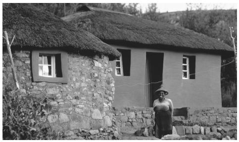 A woman standing by a row of thatched houses. Over 80 percent of Lesotho's population lives in the country's lowland area.