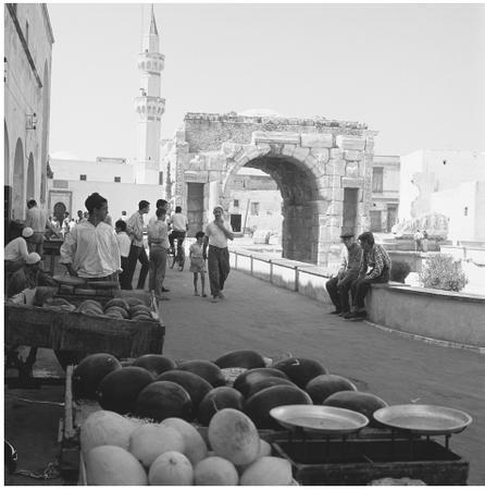 Men gather with carts of melons near the Roman arch dedicated to Marcus Aurelius in Tripoli.