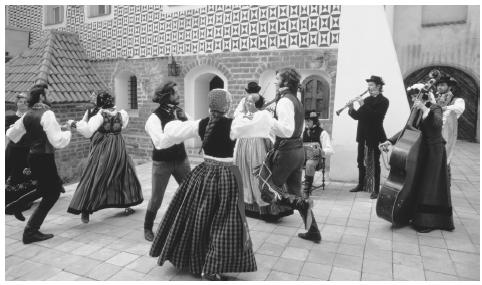 A group of Lithuanian folk dancers and musicians perform in a Vilnius public square.