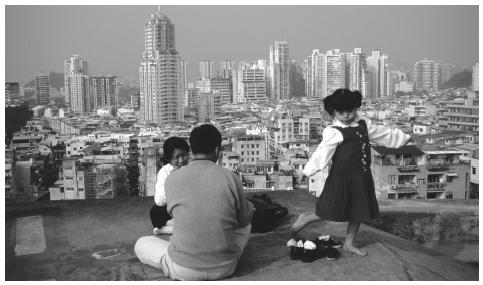 A family relaxing on a rooftop overlooking the cityscape. Despite continued Chinese dependence on larger, extended families, the nuclear family is most pervasive in Macau.