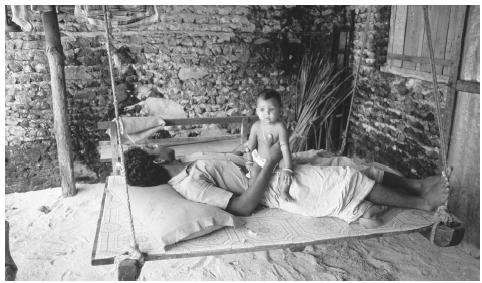 A Himmafushi Island man relaxes with his child. Most Maldivian households consist of nuclear families.