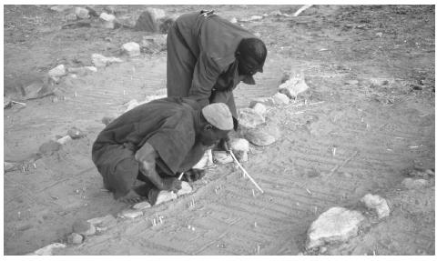 Two Dogon people perform a divination ritual using the prints left in the sand by a jackal. An estimated 19 percent of Mali's population follows traditional religious practices.