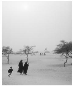 A few Tuareg people outside Timbuktu during a dust storm. Conflicts between the Tuareg and the Malian government improved after the signing of a 1994 peace accord.