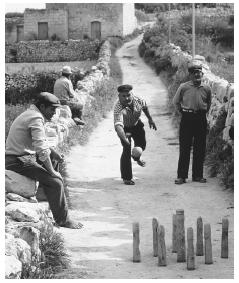 Men play brilli, a form of bowling often called ninepins, on a narrow street in Gozo, Malta.