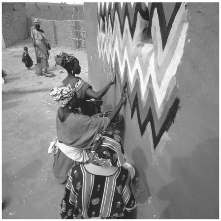 A group of women painting a hut. Mauritanian houses have few wall decorations and sparse furniture.