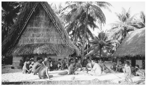 Men gather for a meeting outside the men's house, a community building where men eat, sleep, and store their canoes. Meetinghouses and feast houses are important places for social interaction among Micronesians.