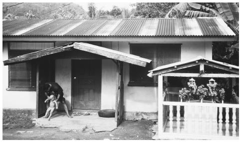 A man with a small child in front of his house in Kolonia, Pohnpei, Caroline Islands. Fathers and mothers equally tend to children in Micronesian society.