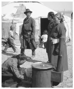 Mongolian nomads cook at a stove outside a yurt. Meat and dairy products are a predominant staple of the diet.