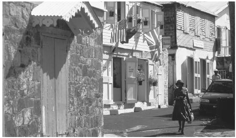 A woman walks along a narrow street in the town of Plymouth.