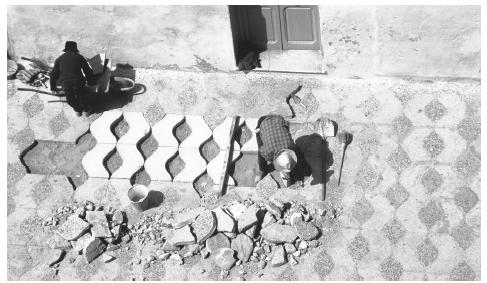 Workers replacing tiles on a Moroccan street.