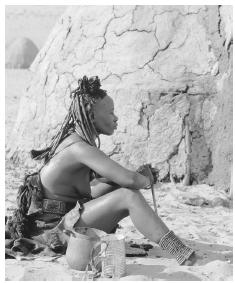 Himba woman next to a mud hut at a Nomadic People Camp in the Skeleton Coast. Namibia was originally inhabited by nomadic hunters, gatherers, and pastoralists.
