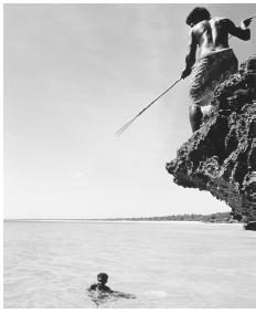 Man fishing from a rock ledge; fish is a national ceremonial food.