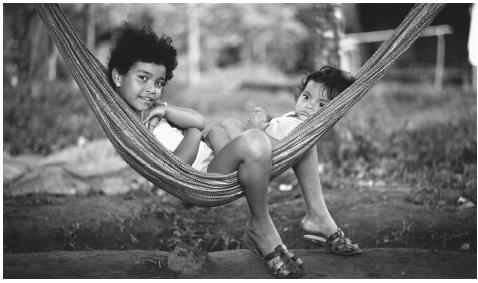 Nicaraguan children relax at their home in Managua. Households are generally comprised of six to eight persons, as an extended family.