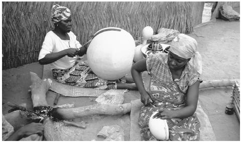 Women engrave designs into yellow calabash gourds. Nigerian art ...