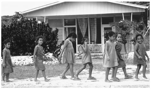 Girls in school uniforms walk along the street. Schooling is compulsory, secular, and free for all children ages 5 to 14.