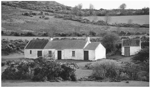 Farmhouse in mountains of Mourn. Northern Ireland has lush green countryside and stout mountains leading to a steep and craggy shoreline.