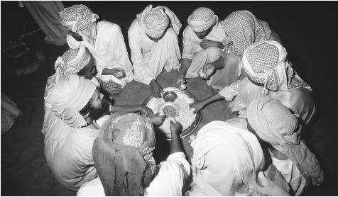 A group of Bedouin eat a meal. Omani cuisine revolves around rice.
