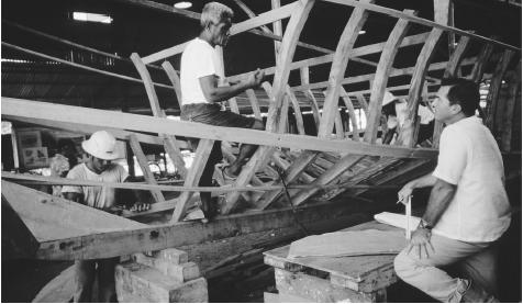 Men building a wooden boat. Fish are Palau's main export, and the annual catch may be up to 780,000 pounds (291,000 kilograms).