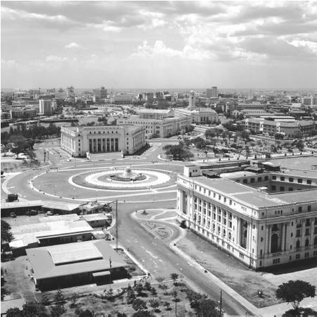 A roundabout with a fountain sits between old buildings in Manila. Some areas of the city were destroyed during World War II, when the country was invaded by Japan and then liberated by the United States.