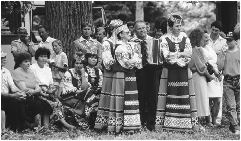 Musicians in traditional Polish costume perform folk music during Swieto Ludowe. The festival commemorates the founding of the town of Narweka.