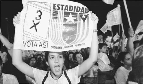 A young woman holds a banner during a pro-statehood demonstration. A U.S. commonwealth since 1952, Puerto Rico has maintained a strong sense of nationalism.