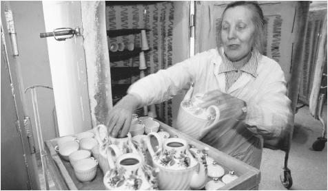 A woman places teapots and teacups in a cabinet, possibly for drying, at the Lomonosov Porcelain Factory. Unemployment for women has increased in the 1990s, especially in the manufacturing sector.