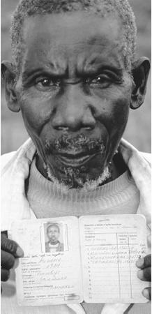 A Batwa holds up his identity card, which notes his ethnic origin. The Batwa have been subject to much discrimination in Rwanda.