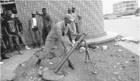 A member of the RFP loads a mortar as crowds watch the frontline. The Rwandan political system is dominated by the military.