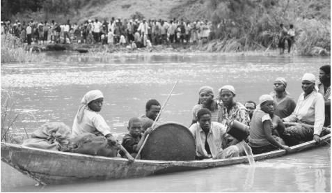 Rwandan refugees cross the Kagera River from Tanzania. In 1999 about 700,000 Tutsi refugees returned to Rwanda from abroad.