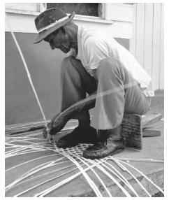 An elderly man weaves a fish trap from dried palm fronds. Fishing is still considered only a man's profession.