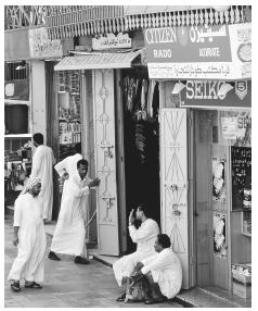 A group of Saudi men gather in front of a store in Jeddah. Men have substantially more rights than women, who must remain out of public view.
