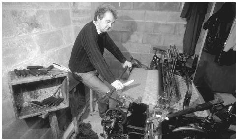 A weaver sits at his loom to weave Harris Tweed, Harris Island, Outer Hebrides. The textiles industry was predominant until 1900.