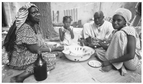 A Senegalese family having a meal together, Ile de Goree. Traditional housekeeping and child-rearing roles are expected from Senegalese women, particularly in rural areas.