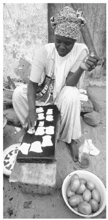 A woman making fish pastilles on the street, Goree Island. Fish products are a major export.
