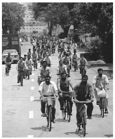 Workers riding bicycles to Sembahong Shipyard, one of the two repair facilities in Singapore. Cars are a symbol of wealth and status.