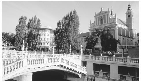 A bridge leading to a Baroque-style church in Ljubljana. Slovenia's towns have many well-preserved buildings representing various styles of architecture dating from the 1100s on.