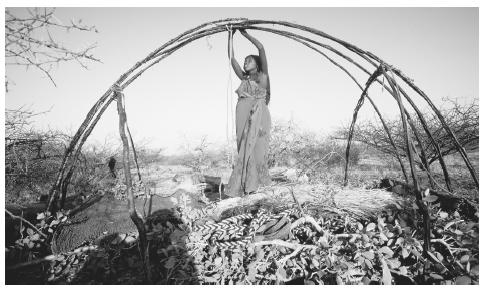 A Somali nomad woman ties roof supports together to reconstruct a portable hut after moving to a new location. The aqal is easy to break down and reassemble.