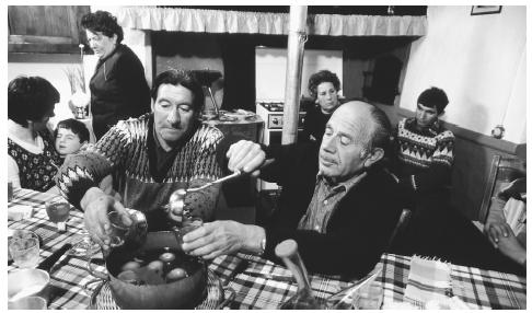 A family enjoys vin cau, or mulled wine, after a large family meal. Meals, especially the midday comida and late-evening cena, are important gathering times in Spain.