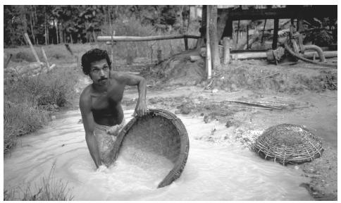 Wading in a pool of brackish water, a man pans for rubies, sapphires and other gems using a basket at one of Sri Lanka's many pit mines.