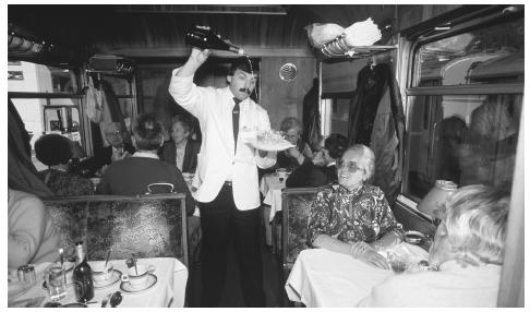 A waiter pours drinks on the Glacier Express, a famous mountain railway that makes a nearly eight-hour journey between Saint Moritz and Zermatt.