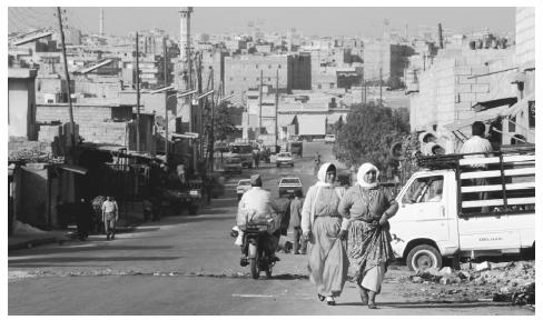 People walking along a street in Aleppo, the nation's second largest city. Protected by rocky terrain, Aleppo was once a fort.