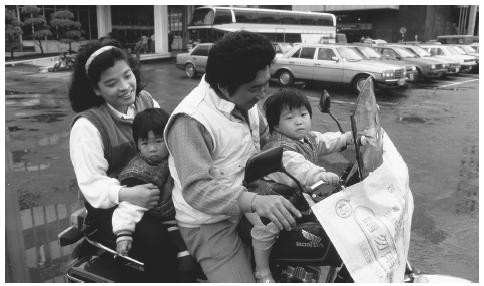 A family rides a motorcycle in Taipei, Taiwan, which is a common mode of transportation.