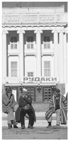 Men wearing traditional Tajikistani clothing sit in front of a Soviet–constructed theater.