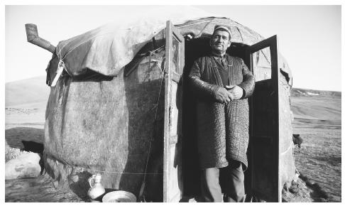A man stands in the doorway of a yurt in a desolate area in the western Pamirs.