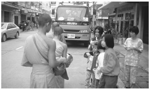 Buddhist monks walk down a street in Thailand. Most young men become Buddhist novices.