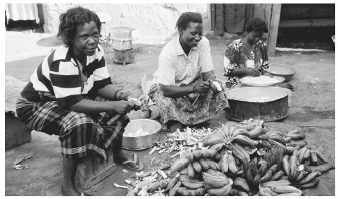 Women preparing food in Kampala. All meals are prepared by women in Uganda; boys over age twelve are banned from the kitchen.