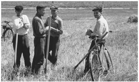 Men talking in a hayfield near Rovno. Workers can now own land again, as collective farms were abolished in 2000.