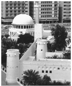 An old fortress surrounded by modern buildings in Abu Dhabi. After 1960, mud-walled communities transformed into commercial centers.