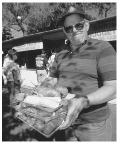 A man holds trays of cooked lobster and corn on the cob at the annual Yarmouth Clam Festival in Yarmouth, Maine.