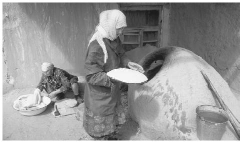 A woman places flat bread dough in an oven, while another woman folds dough in a large bowl, Old Town, Khiva. Families are patriarchal, but mothers run the households.
